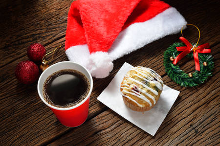 coffee and cake: Paper coffee cup and cake surrounded by Christmas decorations on wooden background