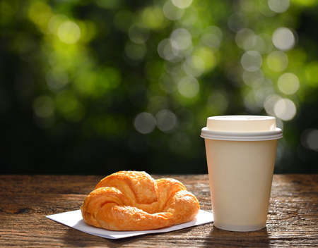 Paper cup of coffee and croissant in the garden,copy space background