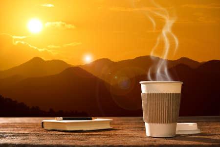 Papieren kopje koffie met berg achtergrond bij zonsopgang Stockfoto