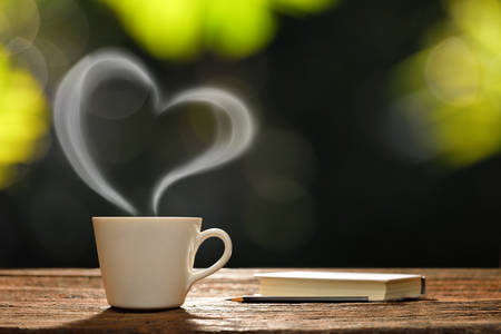 tea hot drink: Cup of coffee with heart-shaped smoke and book in the garden Stock Photo