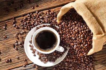 Kop koffie en koffiebonen op houten lijst Stockfoto - 50024589