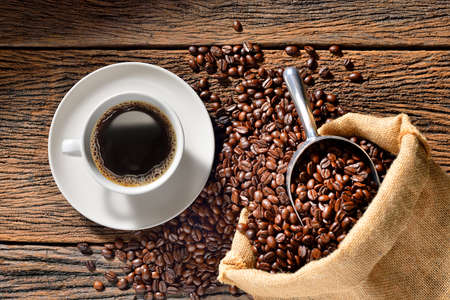 Cup of coffee and coffee beans on wooden table