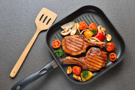 pans: Grilled pork chops and vegetables on the grill pan