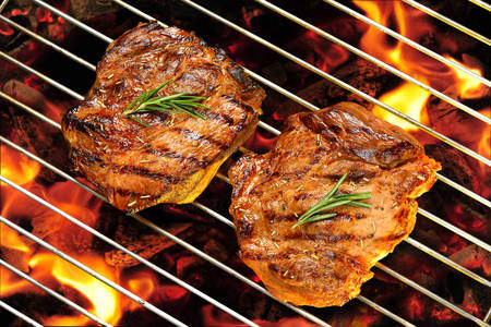 Grilled pork steak on the flaming grill Stock Photo