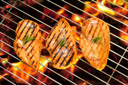 hot breast: Grilled chicken breast on the flaming grill Stock Photo