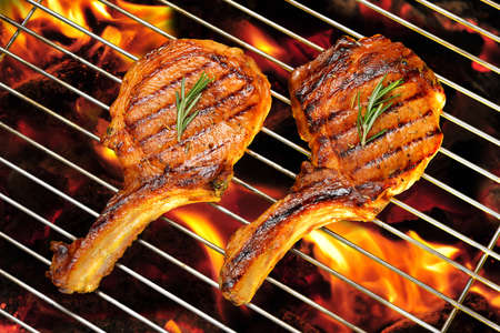 pork: Grilled pork chops on the flaming grill Stock Photo