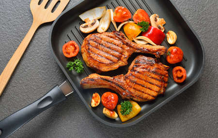 pork chops: Grilled pork chops and vegetables on the grill pan