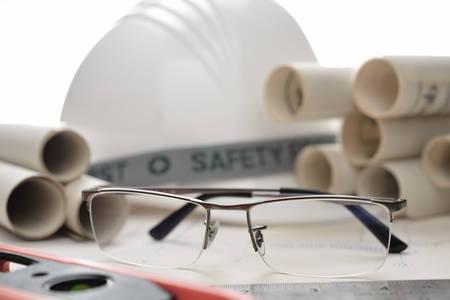 personas leyendo: anteojos de negocios con planes de construcción en el emplazamiento de la obra