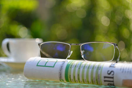 person reading: Businessman eyeglasses on business newspaper in the park