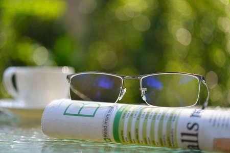 personas leyendo: gafas de negocios en el periódico de negocios en el parque Foto de archivo