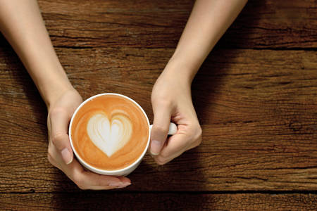 espresso: Woman holding cup of coffee latte, with heart shape