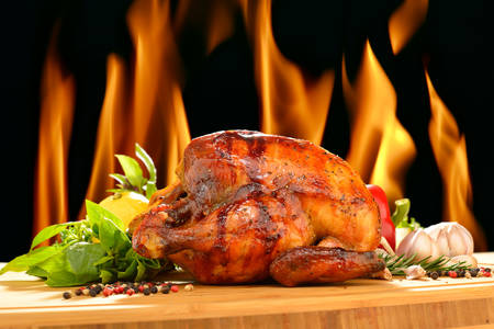 Roasted chicken and various vegetables on a chopping wood 写真素材