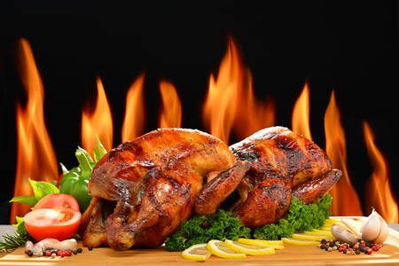 Roasted chicken and various vegetables on a chopping wood Stock Photo