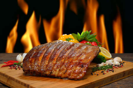 Grilled pork ribs and various vegetables on a chopping wood Imagens