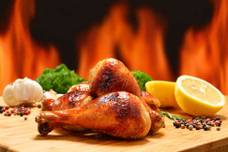 grilled vegetables: Grilled chicken legs and various vegetables on a chopping wood Stock Photo