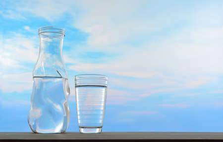 Fresh and clean drinking water in jug and glass on sky background Stock Photo