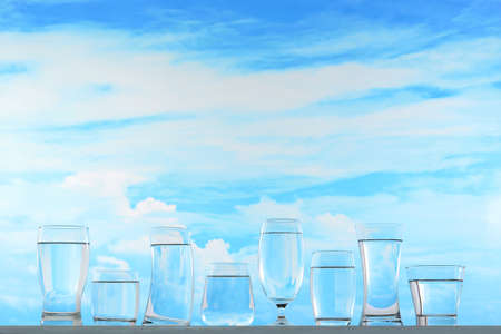 Fresh and clean drinking water in assortment of glasses on sky background