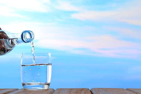 agua potable fresca y limpia que se vierte de la botella en el vidrio en el fondo del cielo