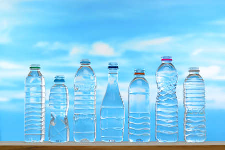 Fresh and clean drinking water in assortment of uncapped bottles on sky background