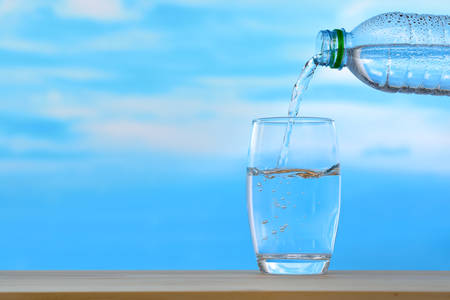Fresh and clean drinking water being poured from bottle into glass on sky background