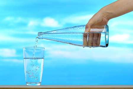 Fresh and clean drinking water being poured from bottle into glass on sky background Stok Fotoğraf - 60732831