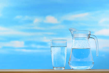 Fresh and clean drinking water in jug and glass on sky background Archivio Fotografico
