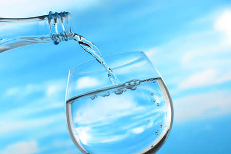 hand water: Fresh and clean drinking water being poured from bottle into glass on sky background