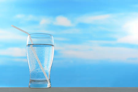 Fresh and clean drinking water in glass with straw on sky background