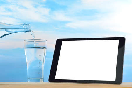 sediento: Tablet PC con agua potable fresca y limpia en el fondo del cielo Foto de archivo