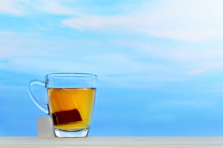 Cup of tea with tea bag on sky background Stock Photo