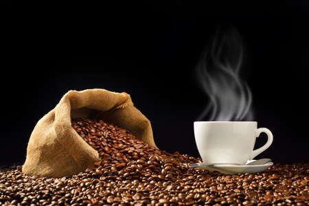 Cup of coffee with smoke and coffee beans in burlap sack on black background Foto de archivo