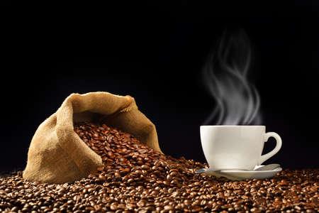 frijoles: Taza de café con granos de café y el humo en saco de arpillera sobre fondo negro Foto de archivo