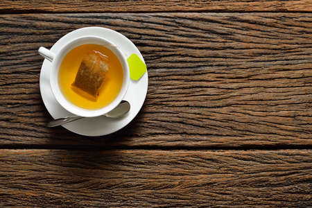 tea table: Top view of a cup of tea with tea bag on wooden table