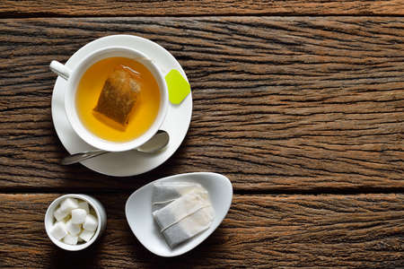 sugar cube: Top view of a cup of tea with tea bag and sugar cube on wooden table Stock Photo
