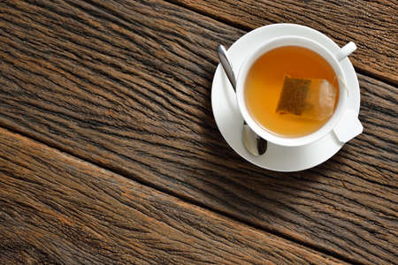Top view of a cup of tea with tea bag on wooden table
