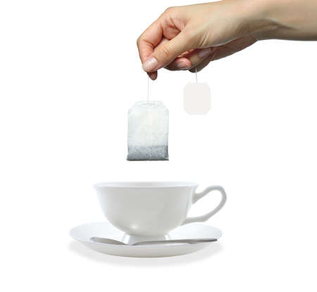 Womans hand holding tea bag isolated on white background Stock Photo