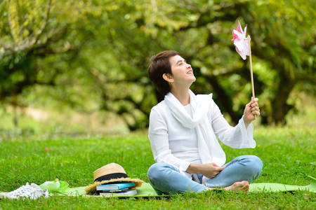 happy asian people: Happy middle aged woman sitting on green grass enjoying the nature (outdoors)