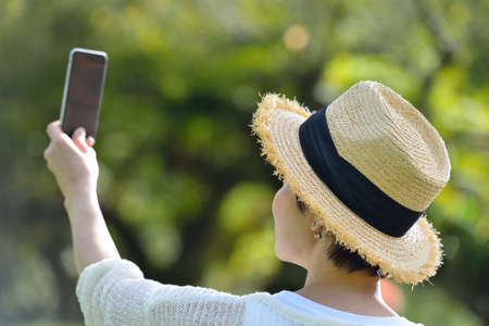 lady on phone: Middle age woman taking a selfie on her phone in the park