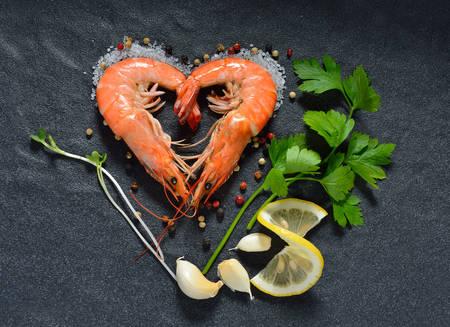 Cooked shrimps,prawns heart shape with seasonings on stone background