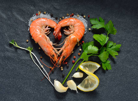 Cooked shrimps,prawns heart shape with seasonings on stone background