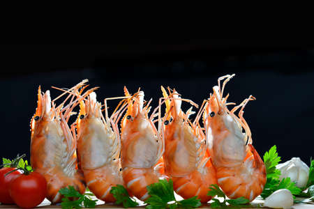 Cooked shrimps,prawns with seasonings on black background