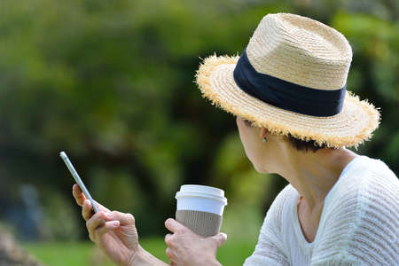 woman on phone: Middle aged woman with a mobile phone in the park Stock Photo