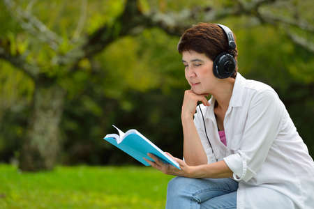 Middle aged woman reading a book and enjoying music with headphones in the park