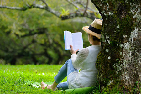 Žena středního věku sedí pod stromem čtení knihy v parku