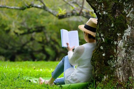 Kobieta w średnim wieku siedzi pod drzewem czyta książkę w parku