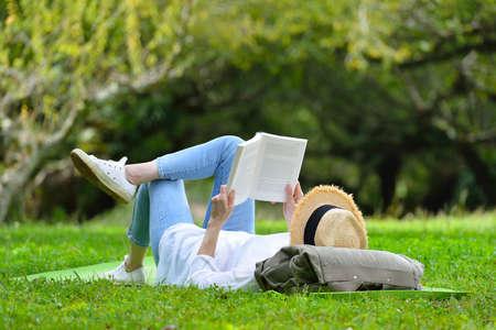 Szczęśliwa kobieta, leżąc na zielonej trawie z książką w parku (na zewnątrz)