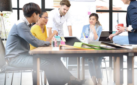 business team: Group of businesspersons having different age in creative business discussing work in the office Stock Photo