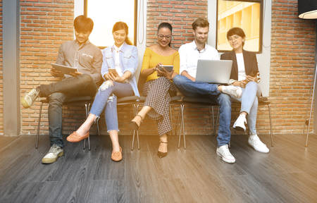 Group of businesspersons with age variety holding electronic devices and gadgets in the office Banque d'images