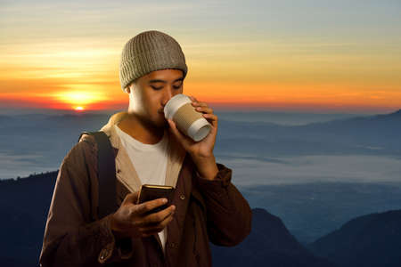 freedom: Young man using smart phone and holding coffee cup on mountain and sun background Stock Photo