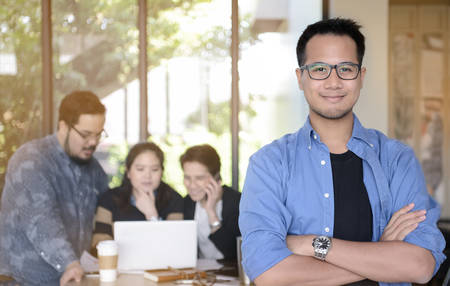 multi age: Young businessman smiling at camera in office